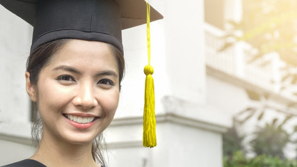 woman student smiles and feel happy in  graduation gowns and cap
