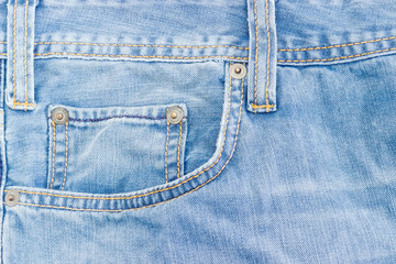 Fragment of the top of the old light blue jeans