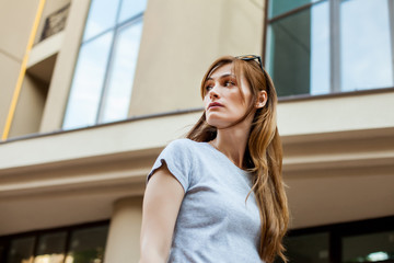 redhead hipster girl in a gray shirt walking in the street. Concept of modern freedom hipster human, close up portrait