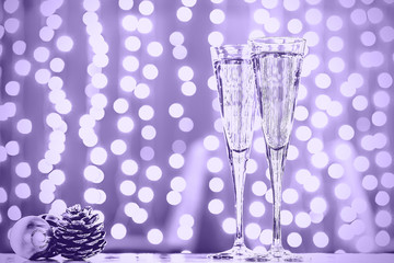 Wall Mural - Two glasses of champagne with Christmas toys. Festive lights bokeh background. Ultra violet tone, color of the year 2018