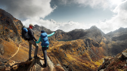 Two Hikers with backpacks in mountains enjoying panoramic on view of mountains