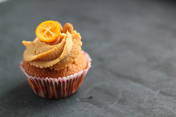 Cream caramel cupcake on black board decorated by almonds