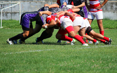 strong rugby players pushing in a scrum