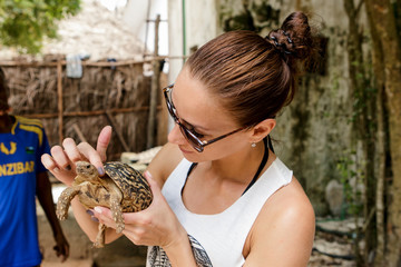 Woman tourist with a small land tortoise