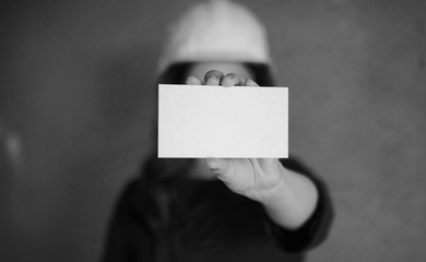 girl with a blank sheet of paper in his hand on construction sit