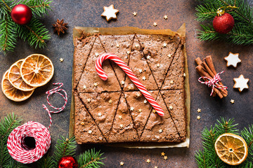 Chocolate brownies with candy cane and Christmas decorations. Top view. Sweet winter holiday food