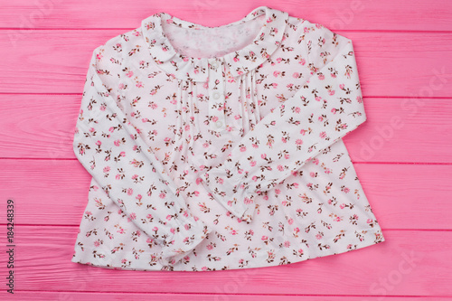 Beautiful floral top on pink wooden table. Ruffle cuffs 858beac51