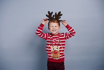 Playful boy with reindeer antlers at studio shot