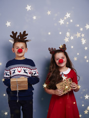 Boy and girl with reindeer antler holding gift box.