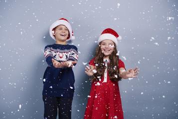 Girl and boy catching snwoflakes
