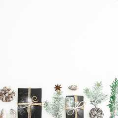 Christmas holiday composition of black gift box, fir branches and pine cones on white background. New year concept. Flat lay. Top view