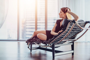 Elegant young woman with fair hair in little black dress lying on armchair supporting her head with hand looking out the panoramic window enjoying cityscape