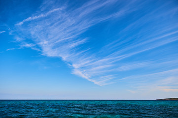Simple blue sky with diagonal stripes of clouds over the sea