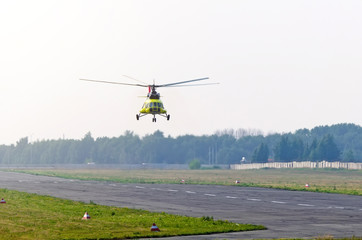 A transport helicopter take off from runway in a small airport.