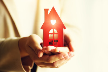 Female hand holding house key, real estate agent. Property insurance, security and cozy home concept. Copy space