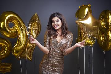 Elegant woman holding glittering sparkler .