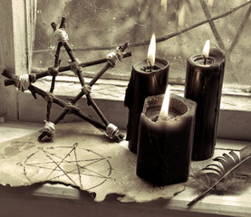 Three black candles, page with pentagram and wooden pentagram by the old window. Occult, esoteric, divination and wicca concept, mystic background