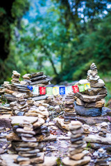 Sanskrit calligraphy of Buddhist Mantra Om Mani Padme Hum on multicolored flags hanging between two meditation stone pile on Annapurna track.
