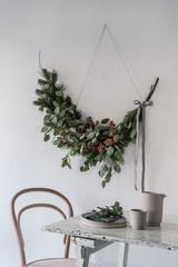 Girlande zu Weihnachten und gedeckter Tisch mit Bugholzstuhl