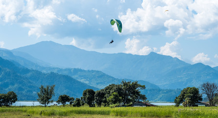 paraglider that flies over meadow, Pokhara region, Nepal. Himalayas mountains on the background.