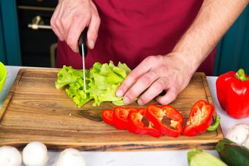 Keuken foto achterwand Koken Hands cut green salad, red pepper, vegetables with knife