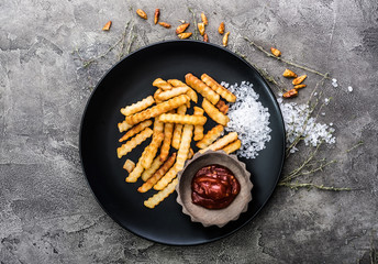 Deep fried french potatoes on dark table, top view