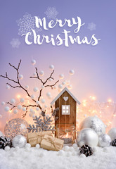 Christmas composition with decorative balls, toy house and candle on snow. Christmas greeting card.