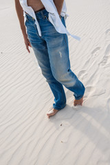 Exhausted man is walking along a sand dune barefoot