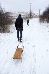 A man walking with sled up to the hill