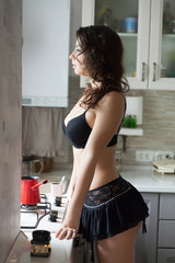 Young sexy woman in the kitchen