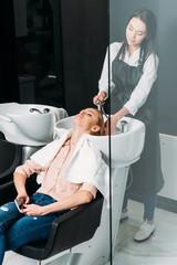 hairdresser in apron washing customer hair