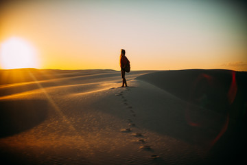 Silhouette of young woman standing on desert