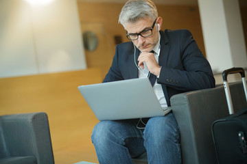 Businessman in waiting room connected wit laptop