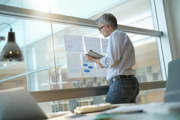 Businessman analyzing results charts hanged on office window