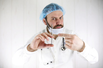 Crazy bearded doctor in a white coat and old syringe