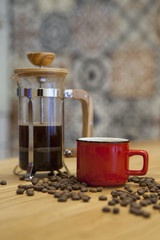 A cup of fresh coffee on a table. Spilled coffee beans and a background coffee maker.