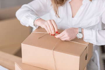 cropped shot of entrepreneur packing customers purchase in cardboard boxes at home office