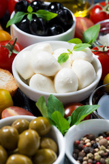 mozzarella, fresh ingredients for the salad and bread, vertical closeup