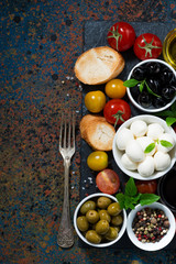 mozzarella, ingredients for the salad and bread and dark background, top view