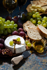 snacks, fruit and Camembert cheese on a dark background, vertical closeup