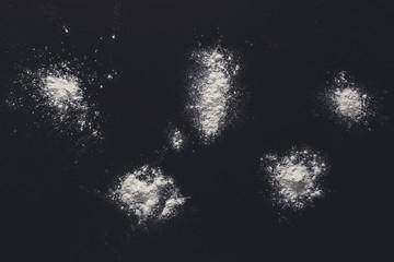 Sprinkled wheat flour splash spots on black background