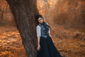 Exquisite lady in a vintage dress for walking with a horse. A beautiful rider stands under a tree. Artistic Photography