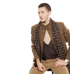 young handsome man in winter clothes with a scarf on white background
