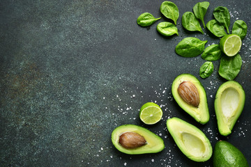 Food background with green vegetables : avocado,baby spinach and lime.Top view with space for text.