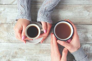 Cups of tea in the hands of men and women. Selective focus.