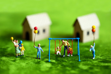 Miniature people with happy family holding balloons in front of wooden house on green background