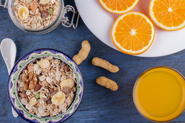 Healthy breakfast. Ceramic bowl with oat flakes, dried fruits, nuts on blue wood background