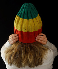 A Bonhams staff member poses for a picture wearing Bob Marley's hat which features in the 'Is This Love'  video and will be sold in an Entertainment Memorabilia auction at Bonhams, in London
