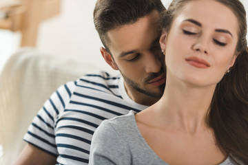 passionate young man kissing neck of girlfriend