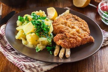 Homemade breaded viennese schnitzel with potato salad and asparagus on a plate